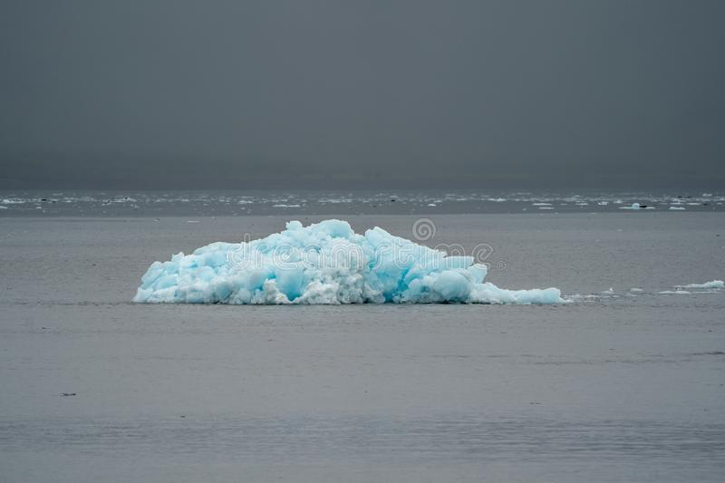 A lone blue iceberg from a glacier sits in Resurrection Bay stock image