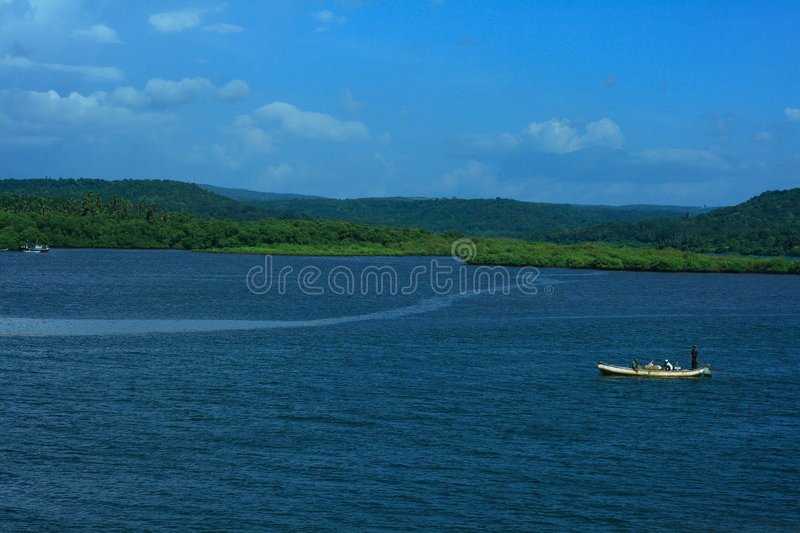 Lone boat in blue sea. Scenic view of lone boat in blue sea with green forested coastline and sky background royalty free stock photography