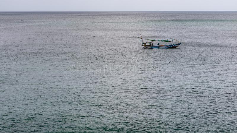 A lone boat floating on the ocean. By itself stock images