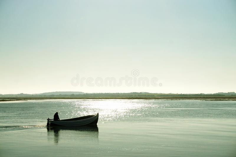 Lone boatman. Silhouetted against the background on a bright sunny morning at Wells Next The Sea Norfolk UK stock photography