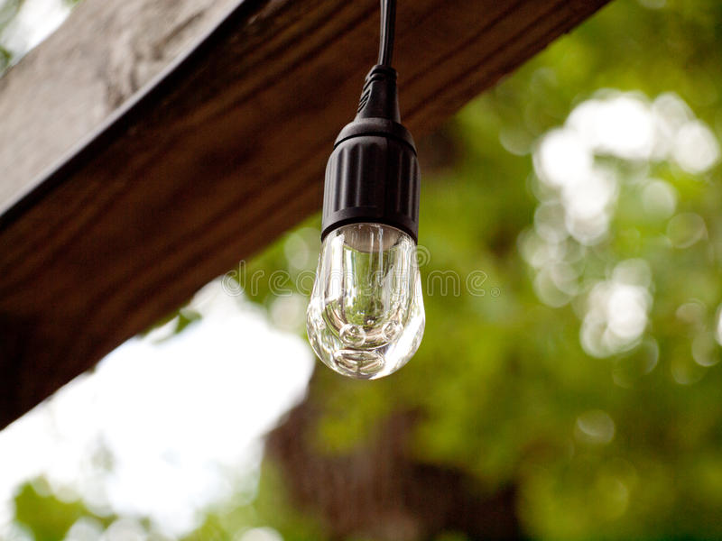 The Lone Bulb Hangs Waiting For The Night. A bulb hanging from a wooden beam awaiting the night sky to lighten the area below royalty free stock photography