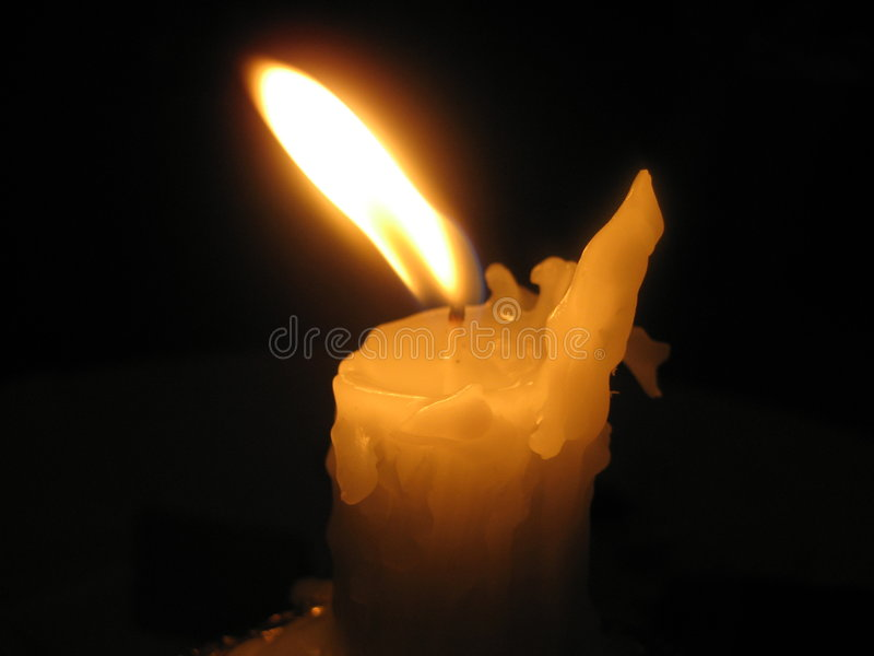 Lone Candle. Wax candle burning against a dark background royalty free stock photo