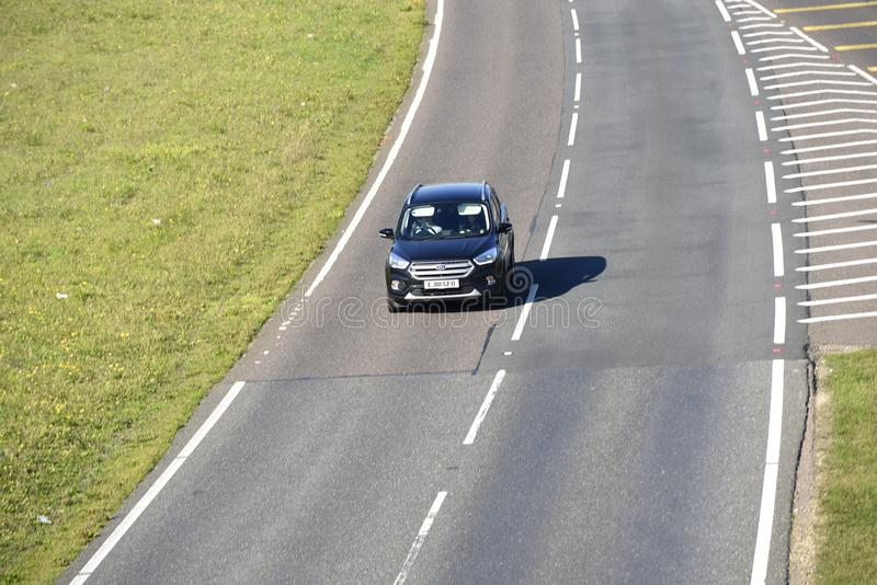 Lone car driving on a stretch of duel carriageway royalty free stock image