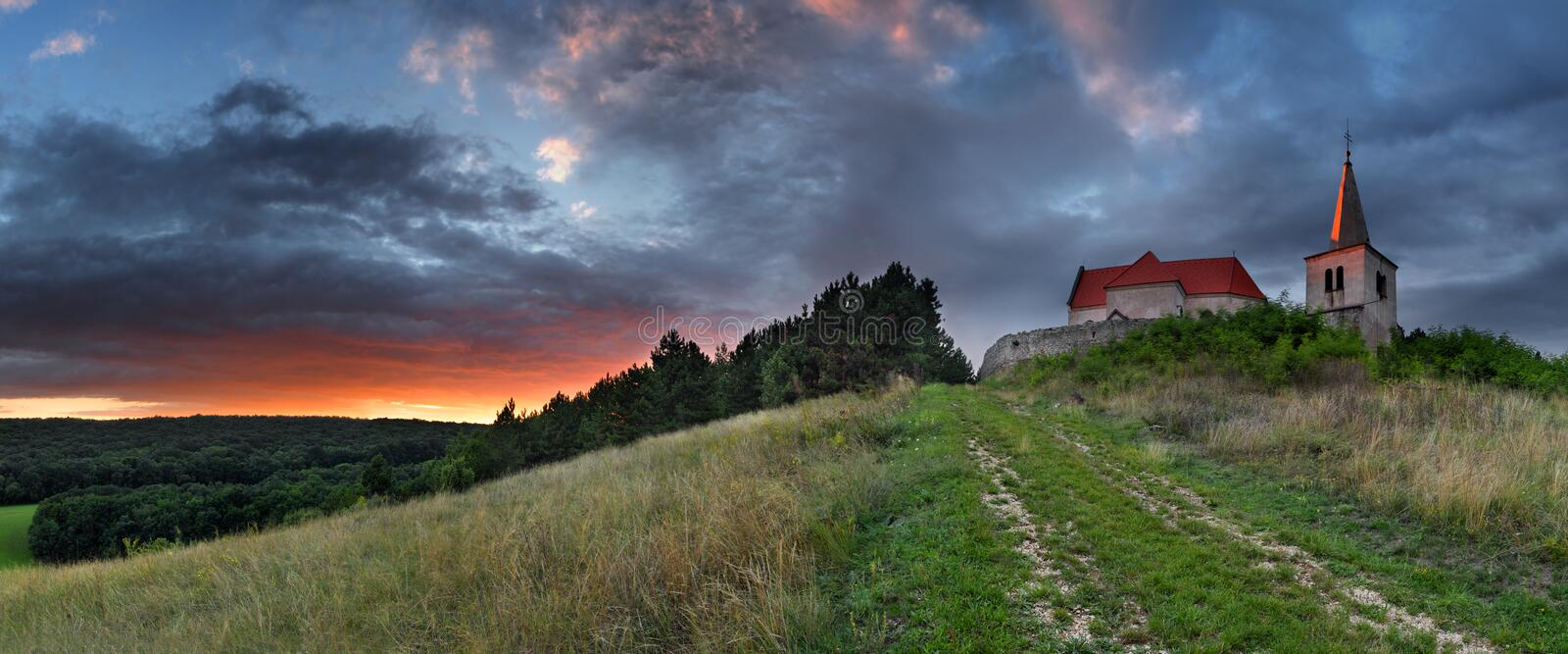Lone Catholic church on meadow. With dramatic clouds stock image
