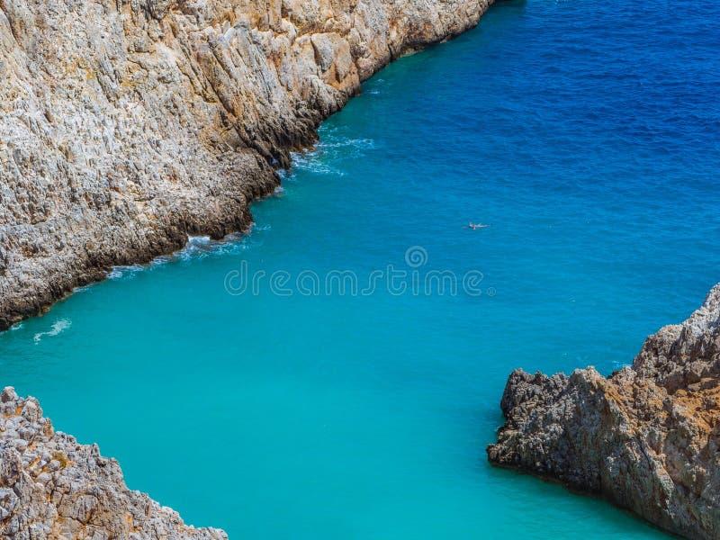 Lone diver swimming. Amazing narrow sea cove, amazing blue water stock image