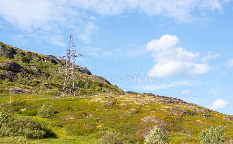 A lone electric iron pole on a hill. A lone electric iron pole on a mountain surrounded by greenery. Wired electricity is the most environmentally friendly type royalty free stock image