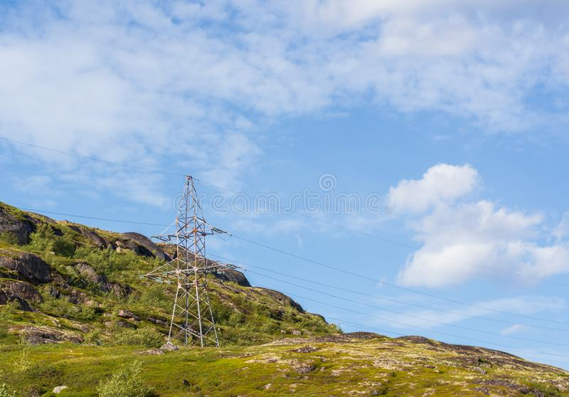 A lone electric iron pole on a hill. A lone electric iron pole on a mountain surrounded by greenery. Wired electricity is the most environmentally friendly type royalty free stock images