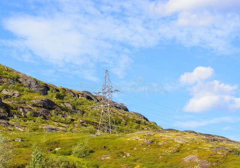 A lone electric iron pole on a hill. A lone electric iron pole on a mountain surrounded by greenery. Wired electricity is the most environmentally friendly type stock images