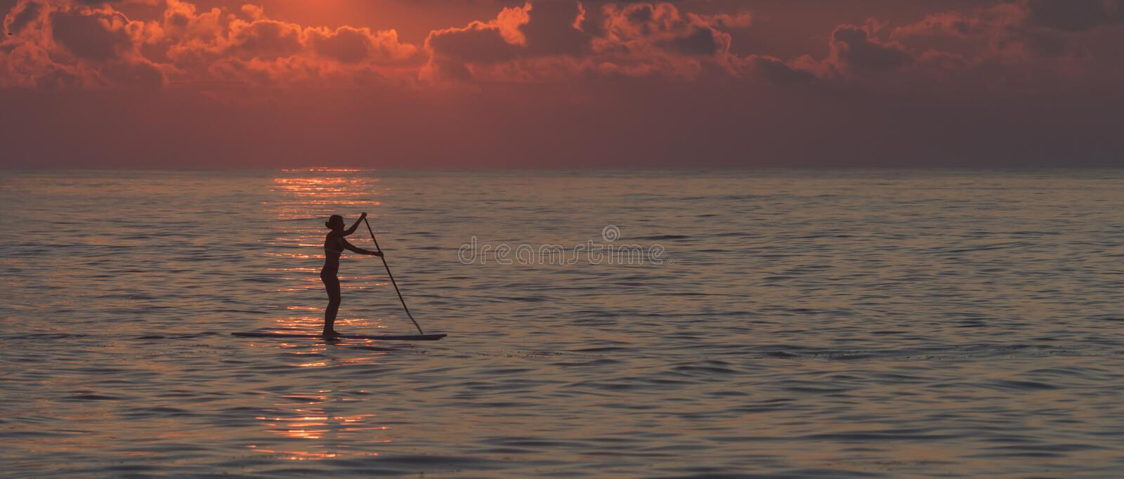 Lone female paddleboarder. Silhouette of lone female paddleboarder standing on her board holding the long paddle on a calm sea at sunset off the coast of Bethany stock photos