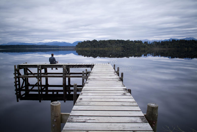 Lone Fisherman. A lone man fishes on the end of a deserted jetty stock image