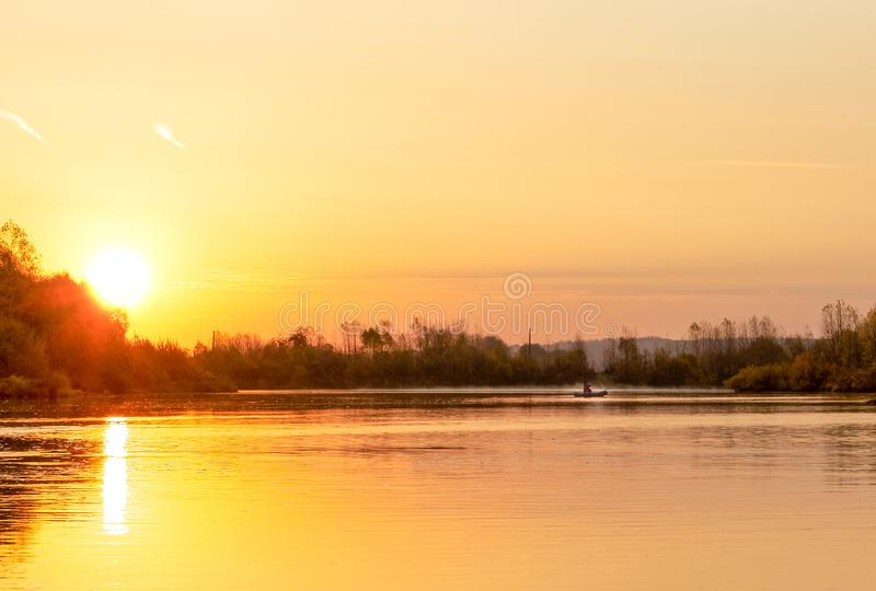 A lone fisherman on a calm river meets dawn on an early autumn m stock image