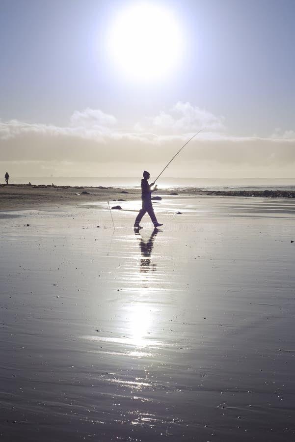 Lone fisherman fishing on the sunny Kerry beach stock photo