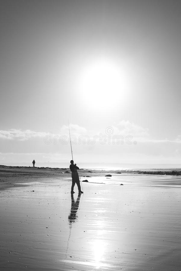 Lone fisherman fishing on the sunset Kerry beach stock images