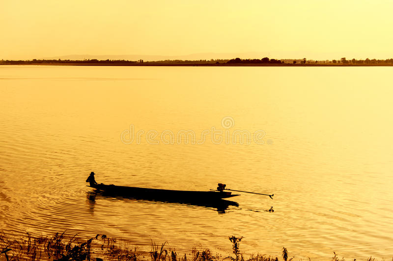 A lone fisherman moves out on a lake. stock image
