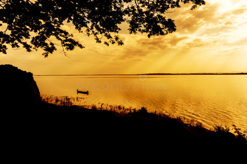 A lone fisherman moves out on a lake. royalty free stock photography