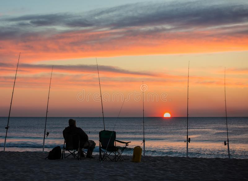 Lone Fisherman at Sunrise on Island Beach State Park, New Jersey with Fishing Poles royalty free stock photos
