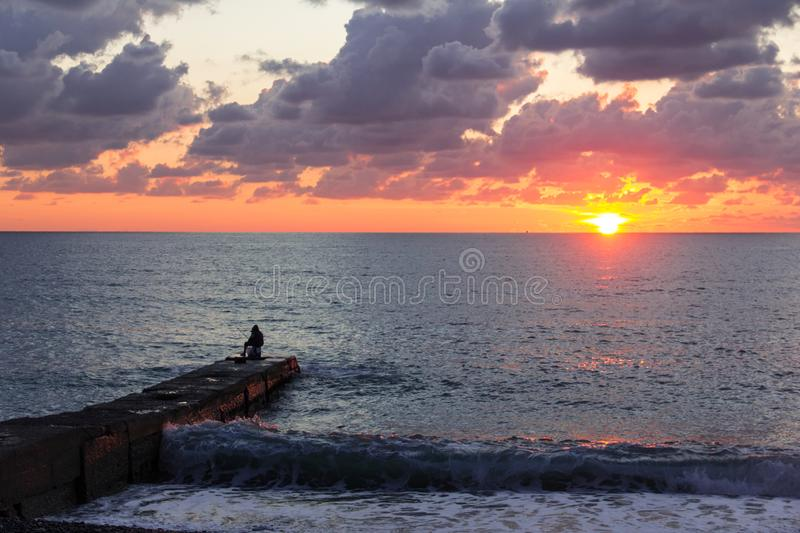 A lone fisherman at sunset in the black sea. Beautiful sunset. the sun sets in the depths of the sea. view of the skyline. silhouette. pier stock photos