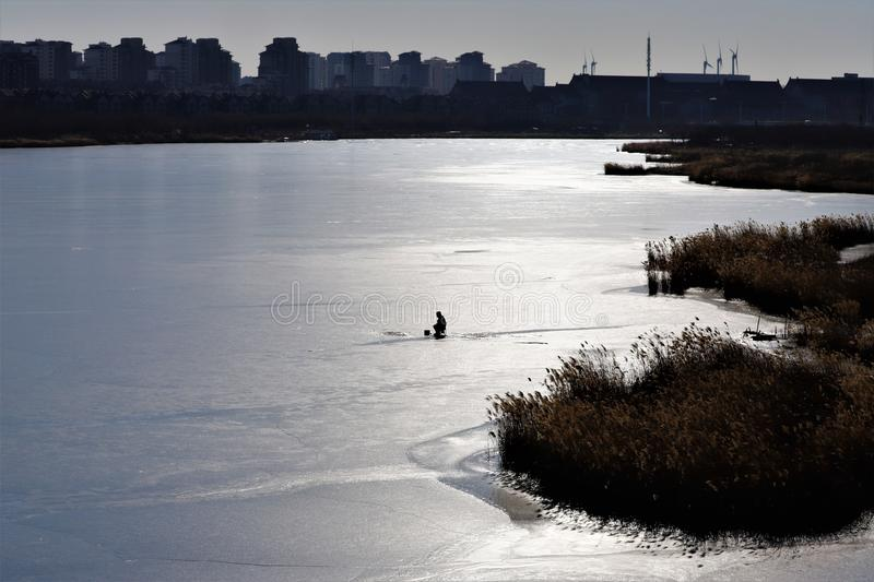 Lone fishernan on the ice, Silent lake, BeiTong Fort. stock photography
