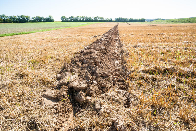 Lone furrow. Close up of a single furrow on an autumnal stubble field stock photo