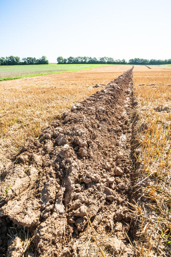 Lone furrow. Close up of a single furrow on an autumnal stubble field royalty free stock photography