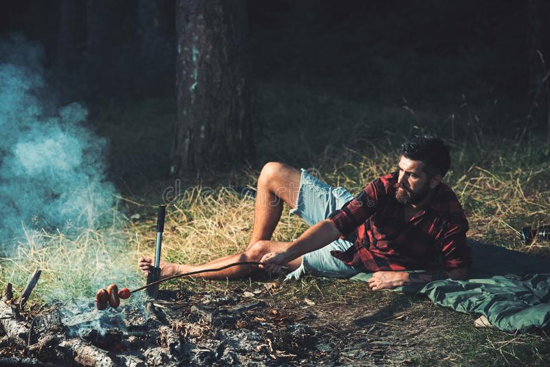 Lone hiker camping in forest. Handsome hipster cooking sausages over fire. Bearded barefoot man lying on grass, unity stock images