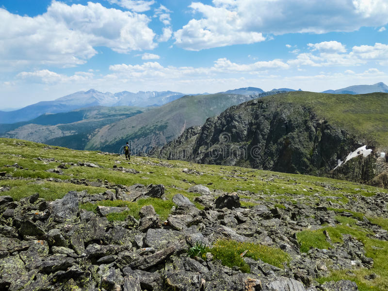 Lone Hiker Near Hallet Peak in Rocky Mountain National Park. A lone hiker takes in the view from a cliff edge near the Hallet Peak summit in Rocky Mountain royalty free stock photo