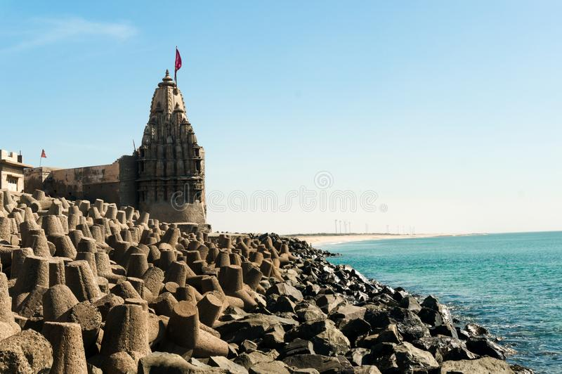 Lone hindu temple with flag on arabian sea coast with wave breakers. The turquoise blue water and blue sky make this holy religious place a perfect tourist and royalty free stock photography