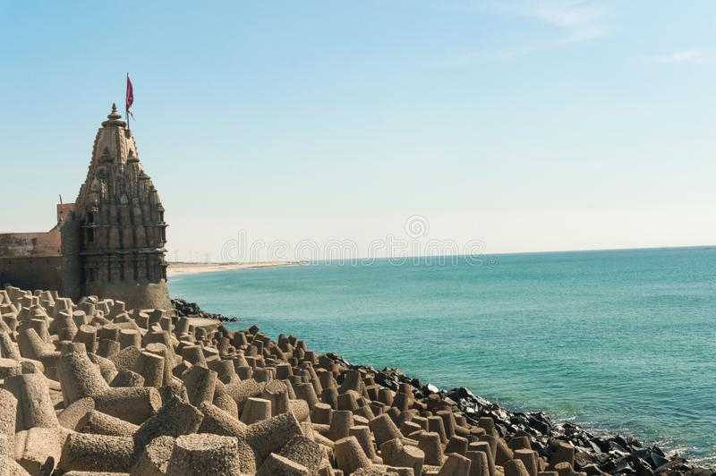 Lone hindu temple with flag on arabian sea coast with wave breakers. The turquoise blue water and blue sky make this holy religious place a perfect tourist and stock photos