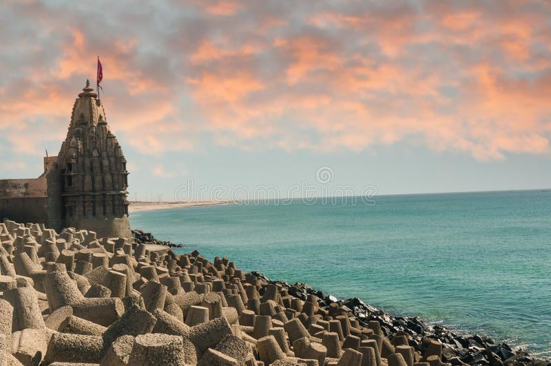 Lone hindu temple with flag on arabian sea coast with wave breakers. The turquoise blue water and blue sky make this holy religious place a perfect tourist and stock images