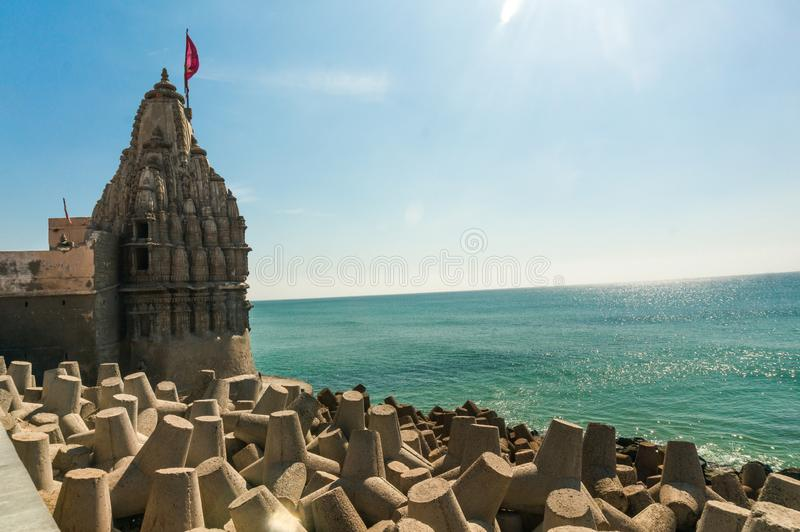 Lone hindu temple with flag on arabian sea coast with wave breakers. The turquoise blue water and blue sky make this holy religious place a perfect tourist and royalty free stock images