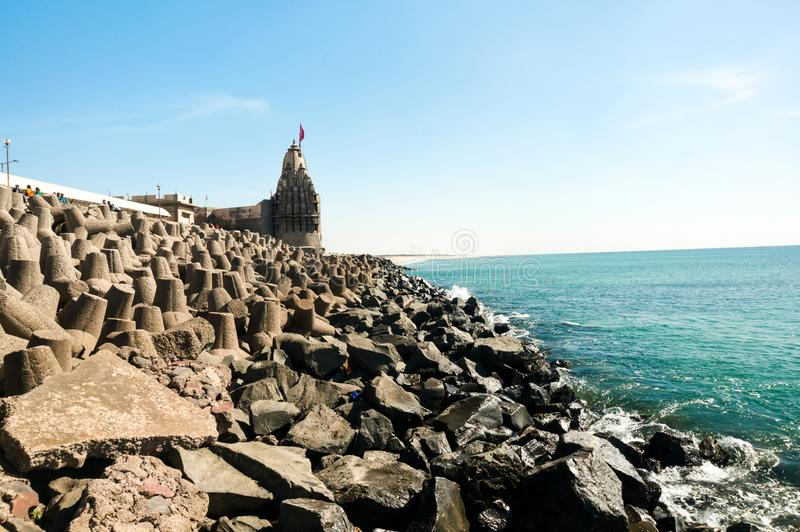 Lone hindu temple with flag on arabian sea coast with wave breakers. The turquoise blue water and blue sky make this holy religious place a perfect tourist and stock photo