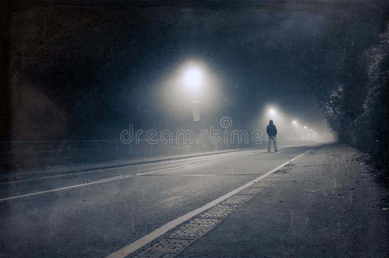 A lone hooded figure standing in the middle of the road on a spooky, foggy night. With a blue, vintage, grunge edit.  royalty free stock images