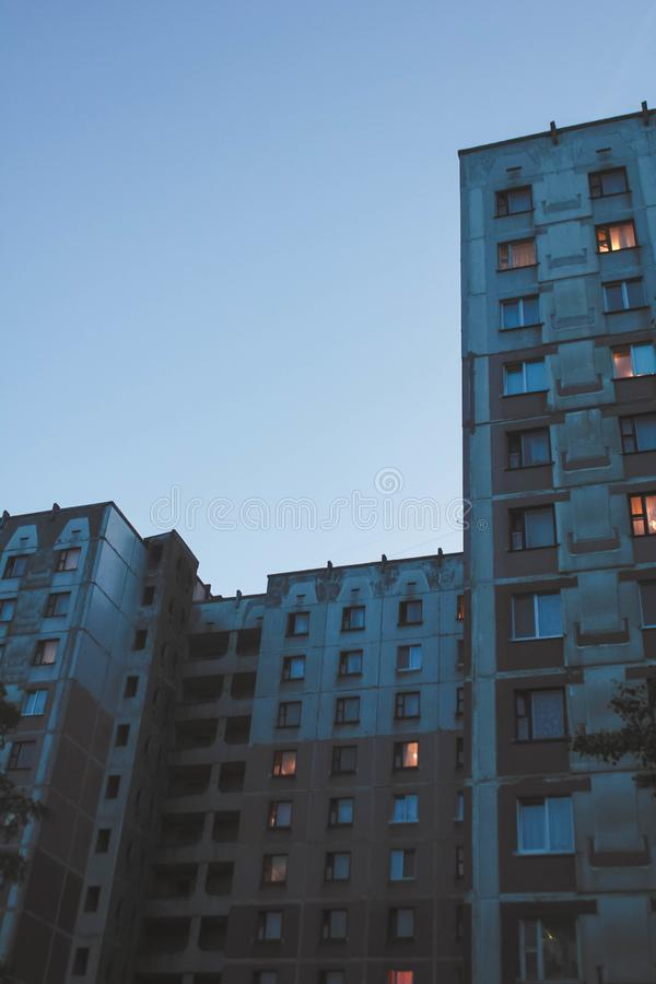 A lone house tending upwards. Only blue, evening sky and high-rise building with glowing lights in it. It looks old and half-abandoned, but there are still royalty free stock photos