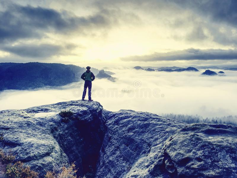 Lone male hiker looks out over high mountains and valley royalty free stock photography