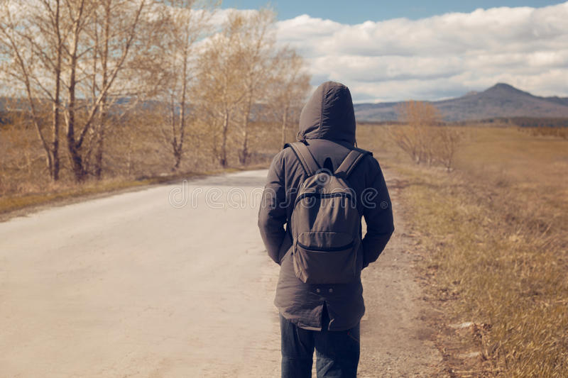 Lone man. A lone man with a backpack walking along the road royalty free stock images