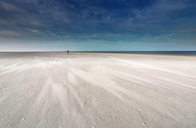 Lone man loopt op het strand van de Noordzee royalty-vrije stock foto's