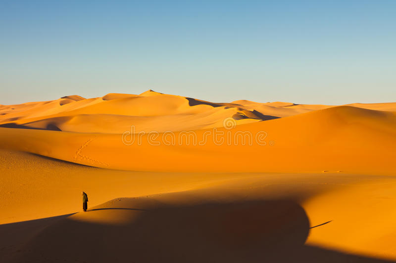Lone Man - Murzuq Desert, Sahara, Libya. Lone man in the sand dunes at sunrise - Murzuq Desert, Sahara, Libya royalty free stock images