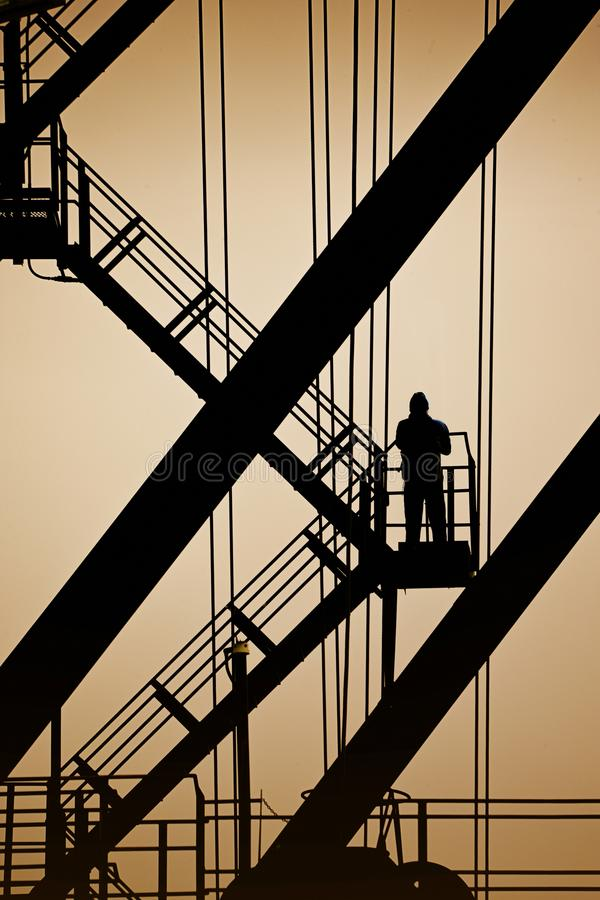 LONE MAN IN SILHOUETTE STANDING ON METAL STEPS OF INDUSTRIAL LADDER. Lone man standing in silhouette on industrial metal structure stairs looking at yellow sky royalty free stock photos