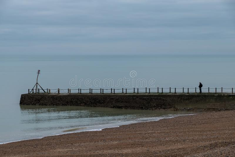 Lone man stands on the jetty on the coastline in Hove, Sussex, UK. Photographed in a cold winter`s day. Lone man stands on the jetty on the coastline in Hove royalty free stock images