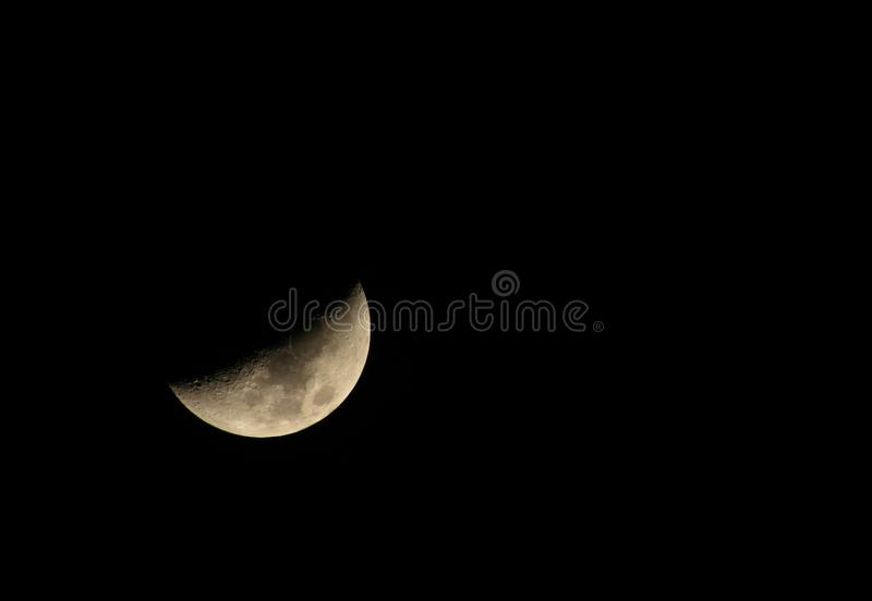 Lone moon. Caught in crescent waxing phase on a black background royalty free stock images