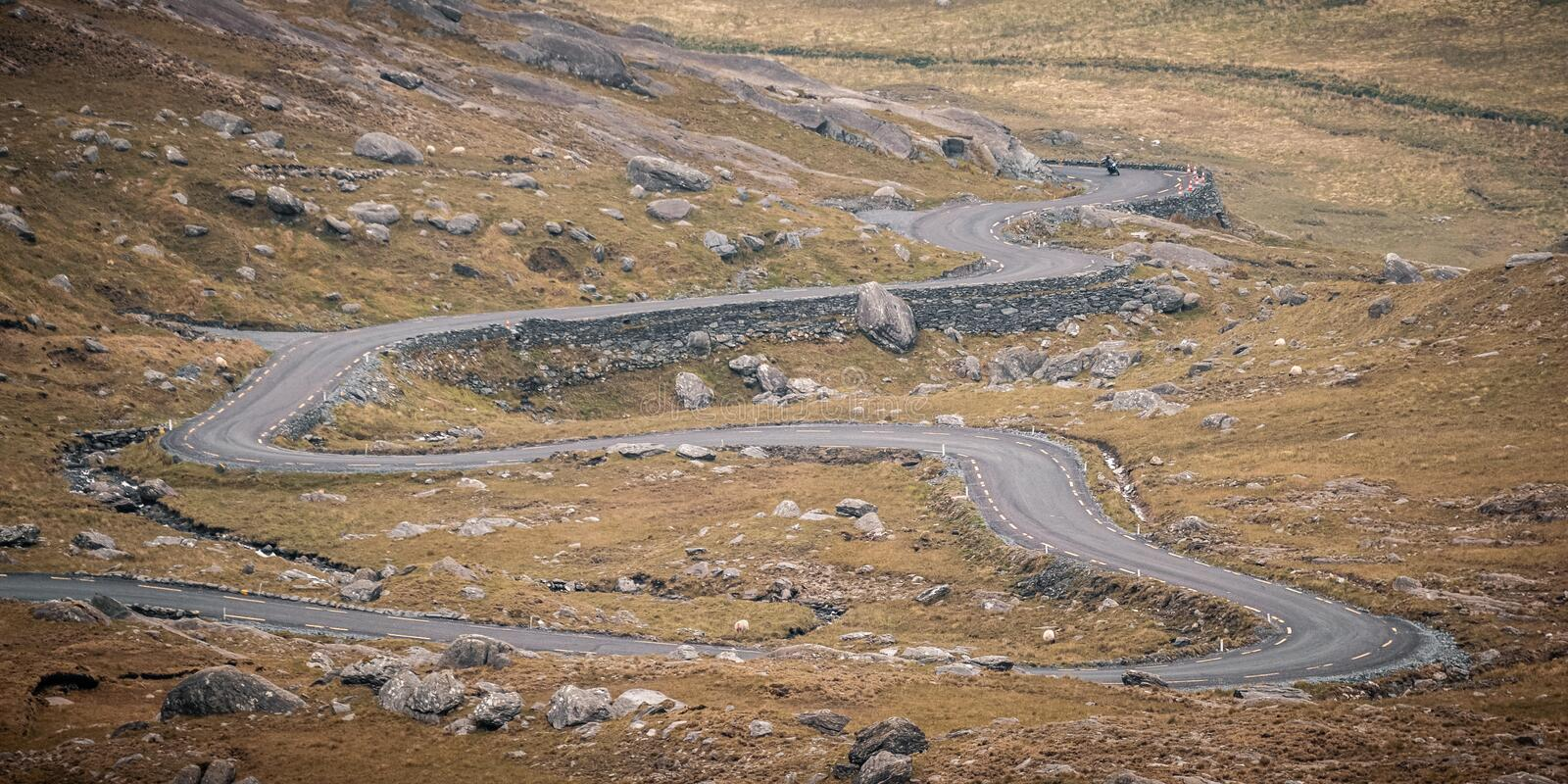Motorcyclist descends Healy Pass in Ireland royalty free stock images