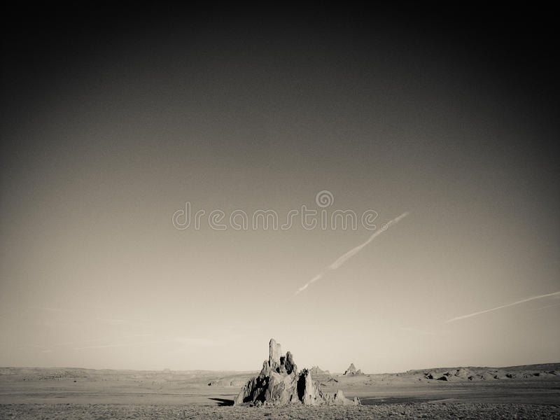 Lone mountain peek rising up from desert. Shiprock rising from the desert floor in Navajo Nation royalty free stock photo