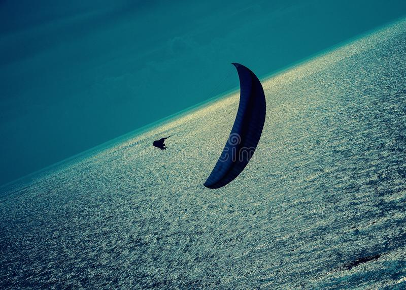 A lone paraglider over a silver sea with dark clouds at dusk. Resubmission; original file ID 102184357. A lone paraglider is a silhouette with a dark blue chute royalty free stock photo