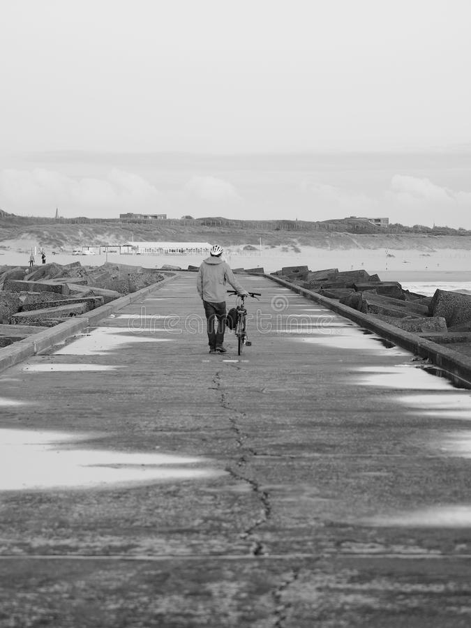 Lone pedestrian pushing bicycle along a concrete pier royalty free stock image