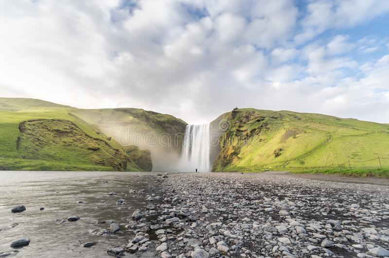 One Person Stands Before the Might of Skogafoss royalty free stock photography