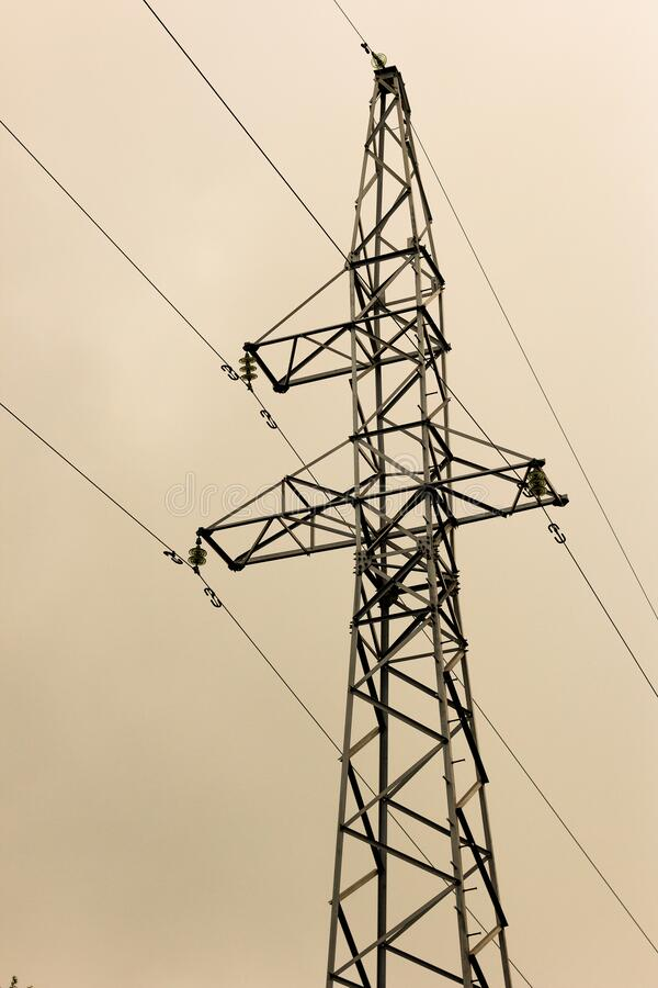 A lone power line mast against a gray overcast sky. A lone power line mast against gray overcast sky royalty free stock photography