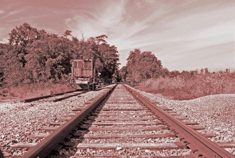 A lone railcar on the railroad tracks. A lone rail car sitting on the railroad tracks royalty free stock image