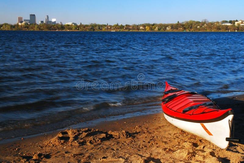 A Lone Red Kayak Awaits a Rider on Lake Calhoun in Minneapolis royalty free stock image