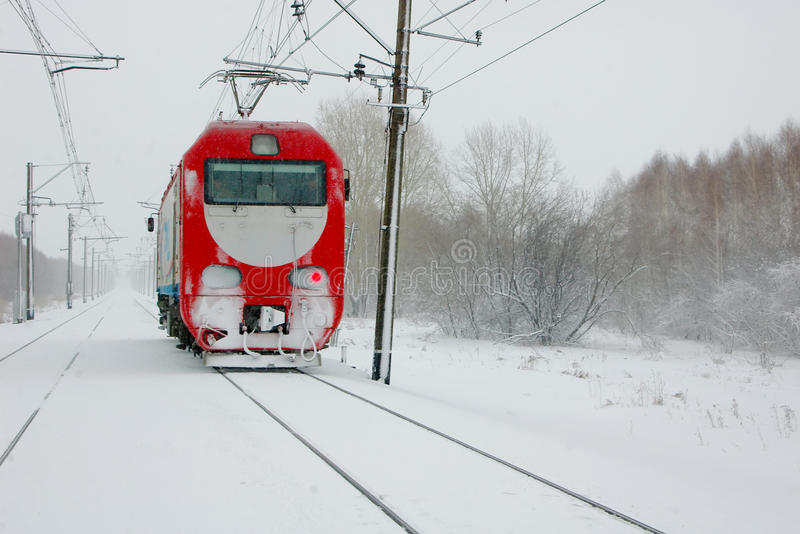 A lone red locomotive hurtling through blizzard. Winter. Railway. A lone red locomotive hurtling through the blizzard and snowstorm stock images