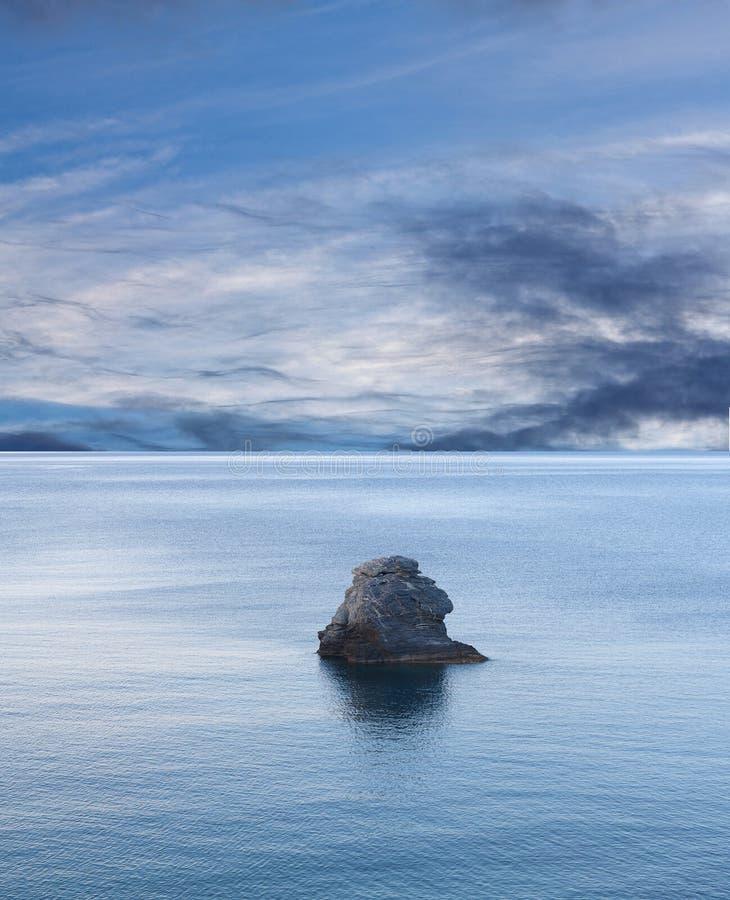 Lone rock over calm sea. Under blue sky. Northen Sporades, Greece stock image